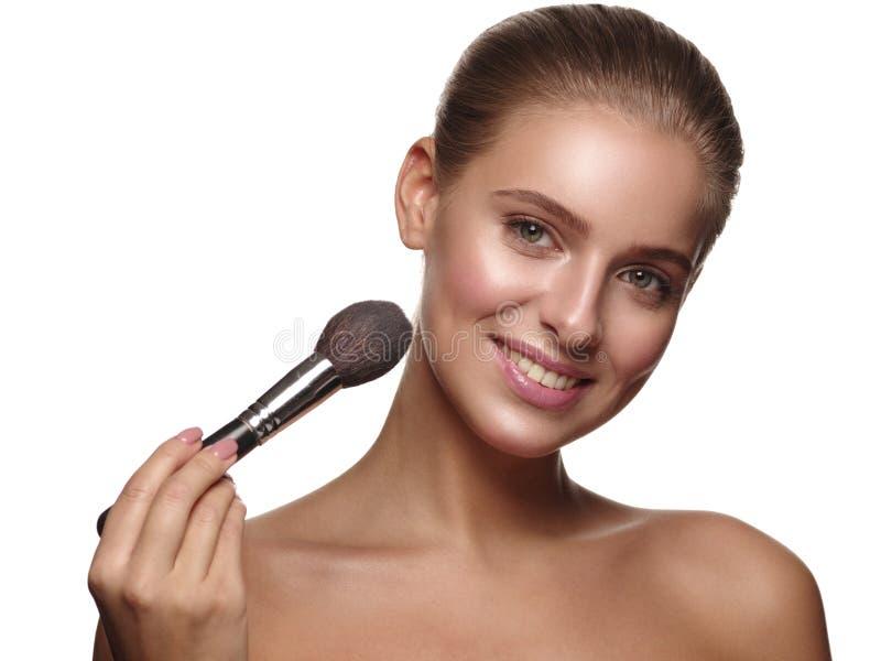 一个女孩的画象有纯净和健康发光的光滑的皮肤的,使用一把刷子在她的手上,申请在她的面孔的每日构成 库存图片