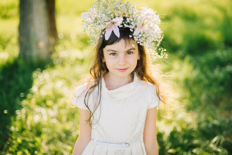 一个女孩的画象有花花圈的在她的头的在草甸 库存图片