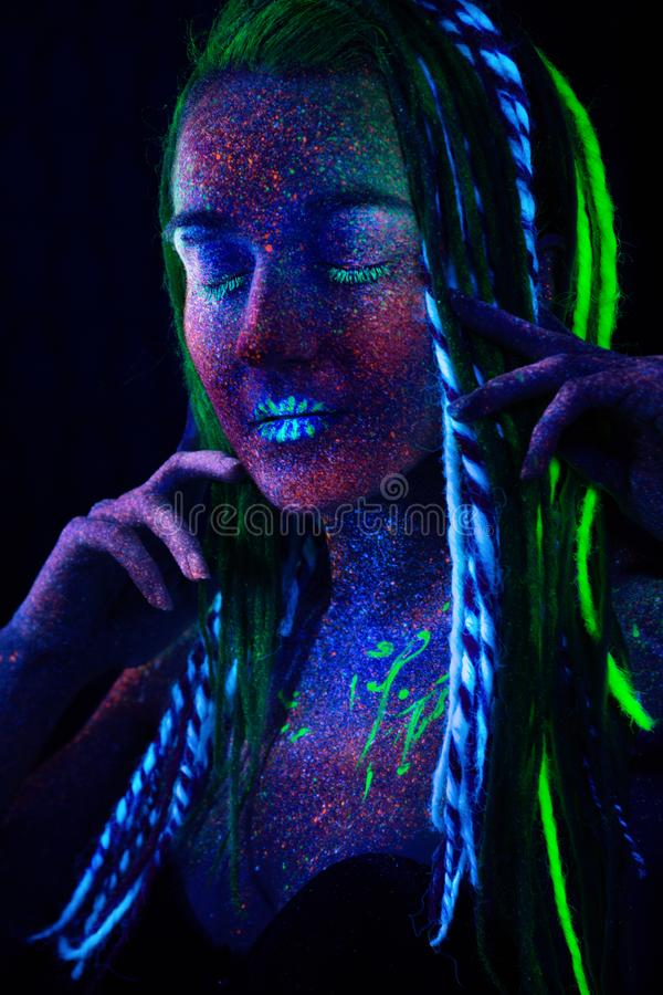 一个女孩的画象有闭合的眼睛和异常的紫外光的 免版税库存照片