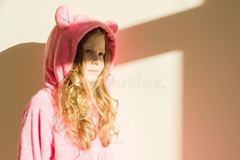 一个女孩的画象软绵绵地温暖的桃红色睡衣的 女孩7岁,白肤金发与长的卷发,在敞篷,看  背景l 库存图片