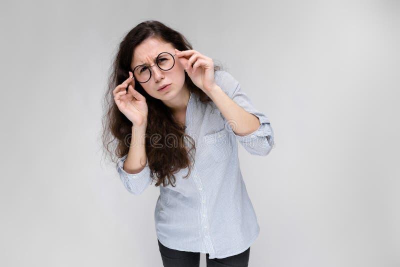 一个女孩的纵向玻璃的 灰色背景的美丽的女孩 轻的女衬衫和黑暗的一个女孩 免版税库存照片
