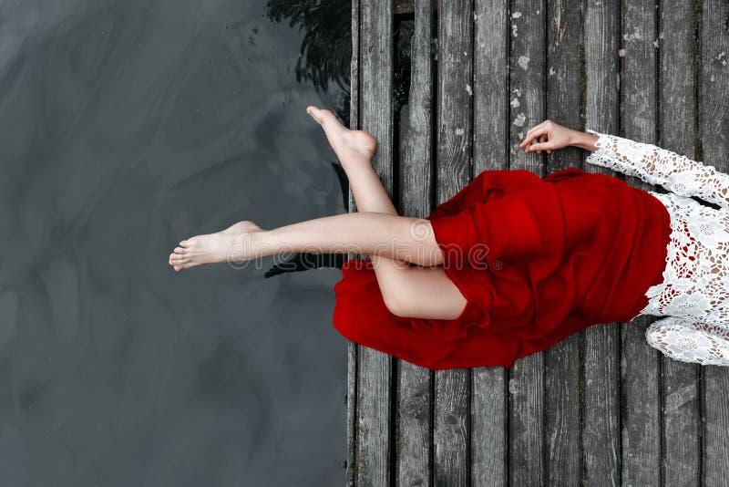 一个女孩的腿一条红色裙子的在桥梁 免版税库存照片