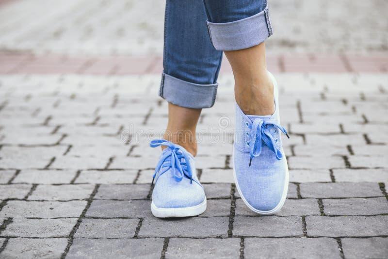 一个女孩的腿牛仔裤和蓝色运动鞋的在边路瓦片,漫步在夏天公园的一个少妇 库存图片