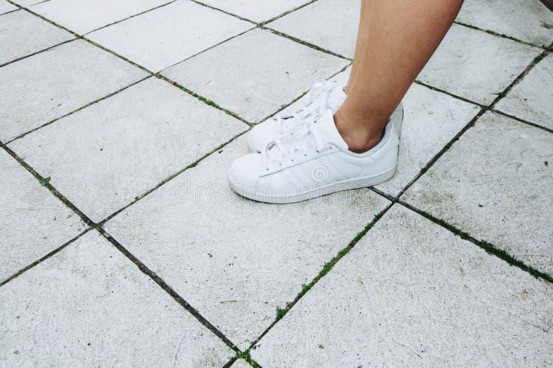 一个女孩的腿白色运动鞋的在一个灰色瓦片 免版税库存照片