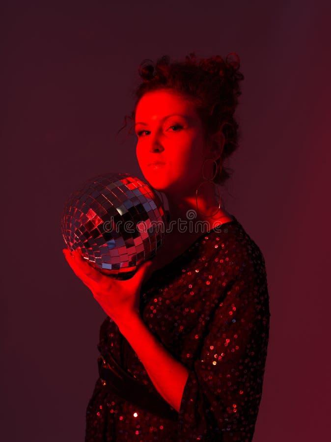 一个女孩的迪斯科式红色照片有迪斯科球的 库存图片