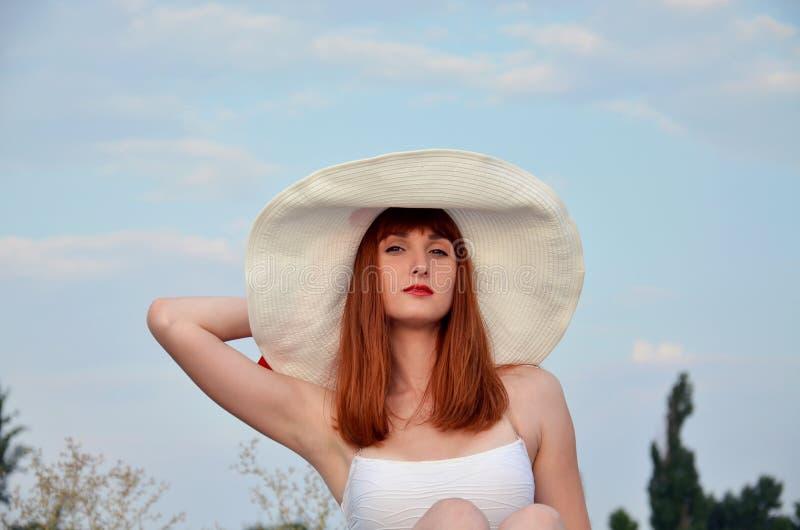 一个女孩的画象一个大白色帽子的 库存照片