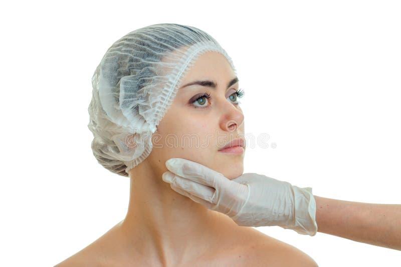一个女孩的画象帽子人的由一位医生的特别身体检查在一只白色手套的手上 库存照片