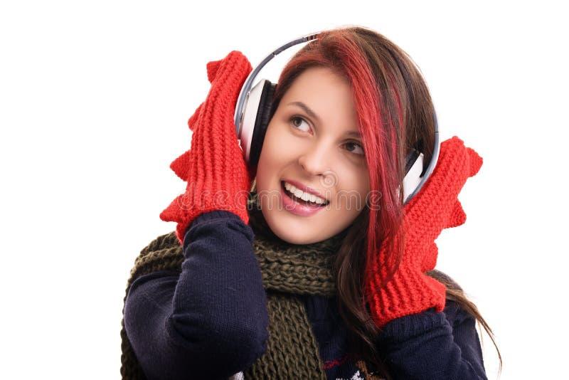 一个女孩的画象有冬天衣裳和耳机的 免版税库存图片