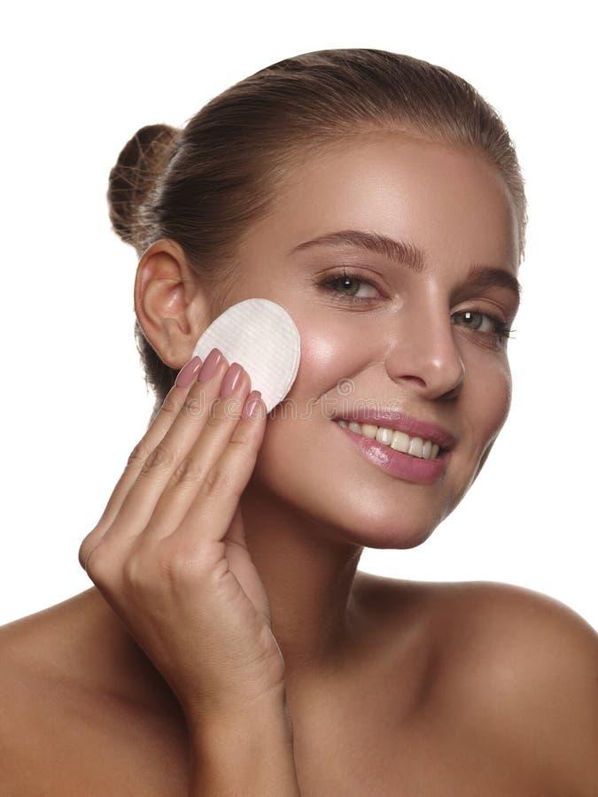 一个女孩的Ortrait有纯净和健康发光的皮肤的没有构成,使用化装棉,做着日报洗涤的做法 图库摄影