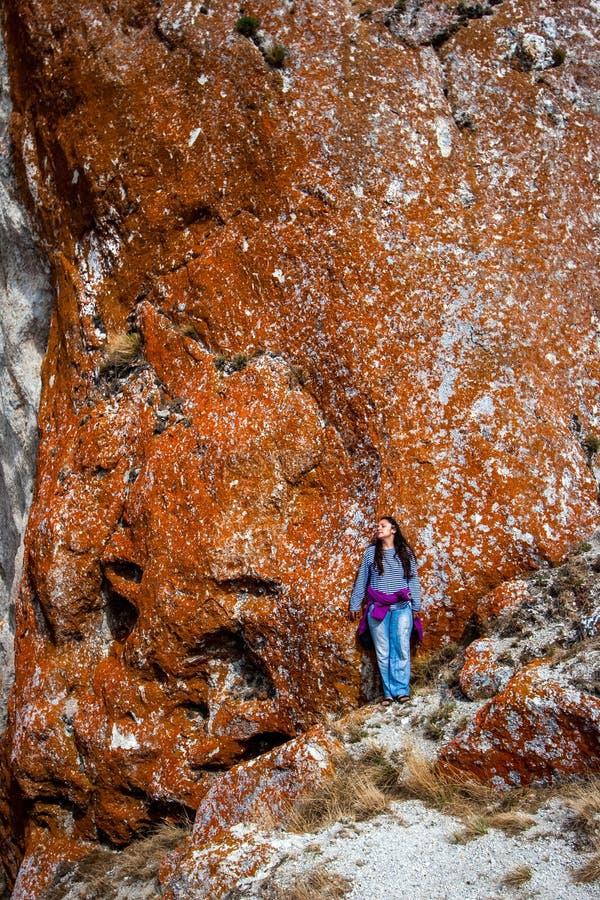 一个女孩站在一堵长着红苔的石墙旁 免版税库存图片