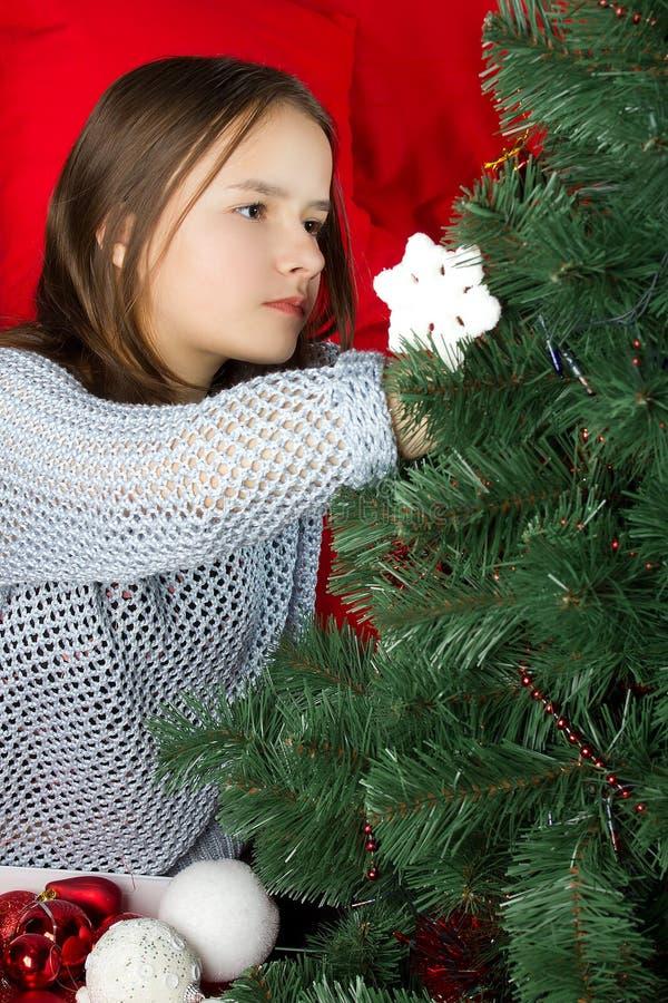 一个女孩装饰一棵圣诞树 图库摄影