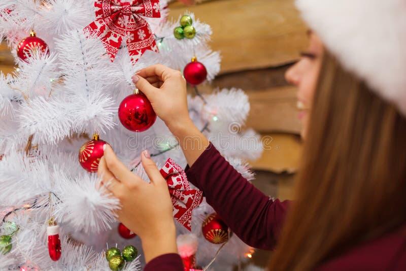 一个女孩装饰与玩具的一棵圣诞树 圣诞节大气 户内 免版税图库摄影