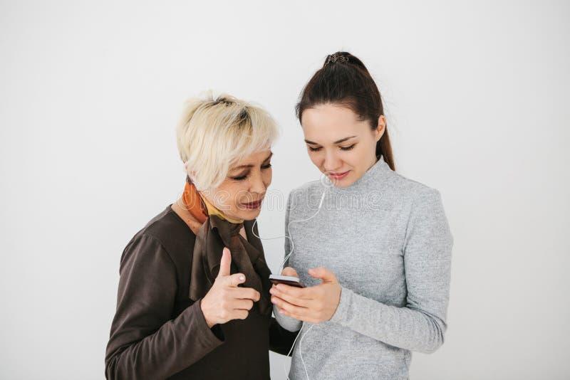 一个女孩解释给一名年长妇女如何使用手机或显示某一应用或教如何使用a 库存照片
