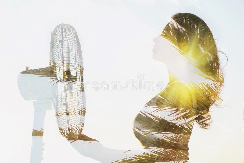 一个女孩身体的两次曝光有爱好者和棕榈树的 库存照片