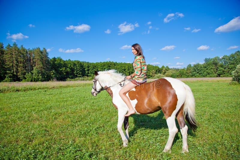 一个女孩骑油漆马 免版税图库摄影