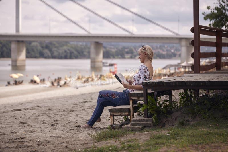 一个女孩,坐在海滩的步,夏天,愉快微笑,读书户外 侧视图 免版税库存照片