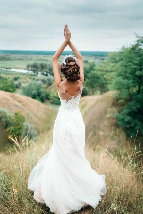 一个女孩,婚礼礼服的新娘,被转动她和凝视入在河和一个美好的大局的距离 免版税库存图片