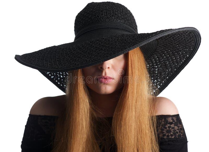 一个女性时装模特儿的画象与在白色隔绝的黑帽会议的 库存照片
