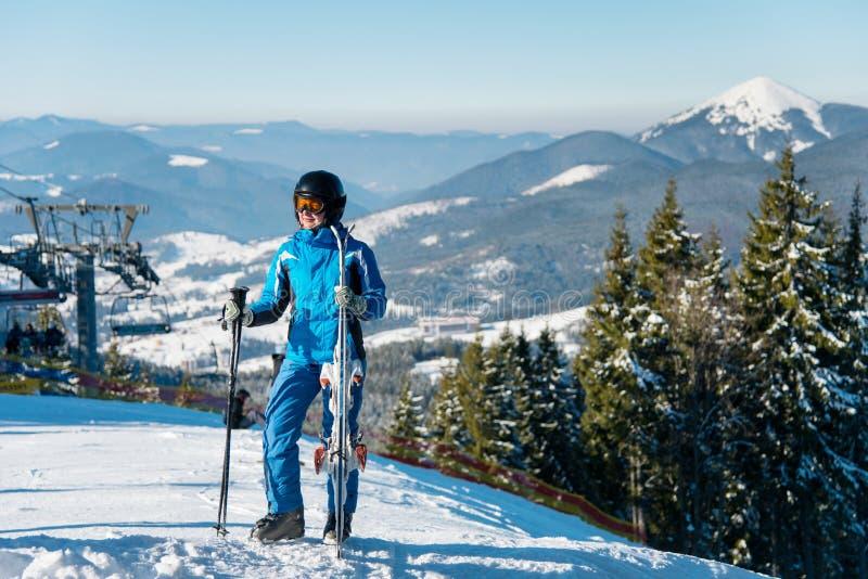 一个女性滑雪者的全长射击摆在与她的滑雪的一座山顶部的冬天运动服的 库存照片