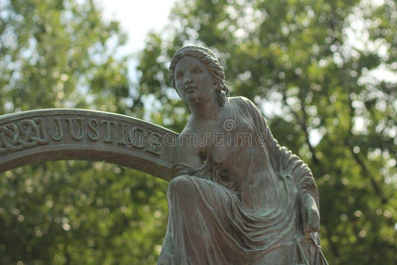 一个女性雕象的特写镜头在与被弄脏的树的一好日子在背景中 免版税库存照片