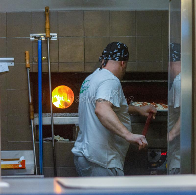 一个好的比萨制造商,当与插入他的一优秀比萨时的烤箱一起使用 免版税库存照片