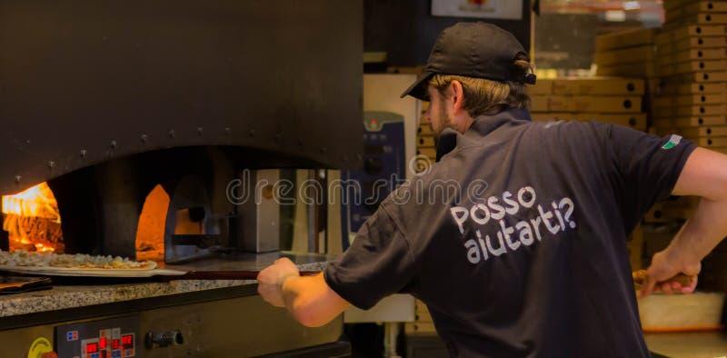 一个好的比萨制造商,当与插入他的一优秀比萨时的烤箱一起使用 免版税图库摄影