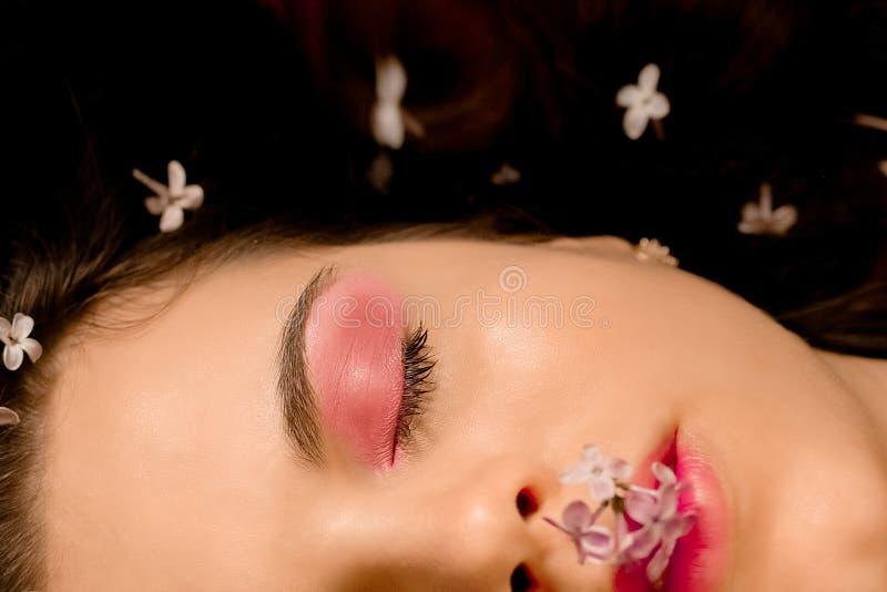 一个妆容鲜艳的美女的肖像 脸上飘着花香,春女,花 免版税库存图片