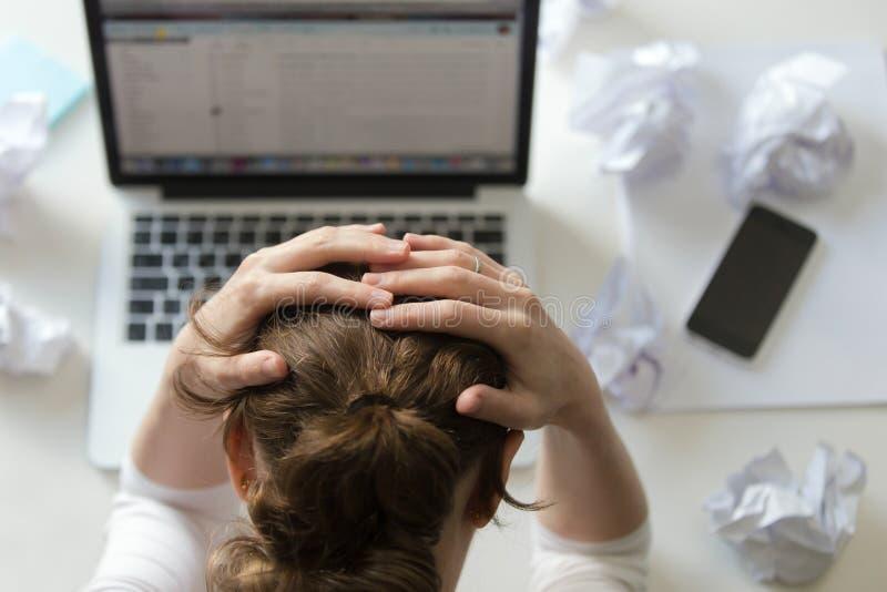 一个妇女劫掠的头的画象在书桌的在膝上型计算机附近 库存照片