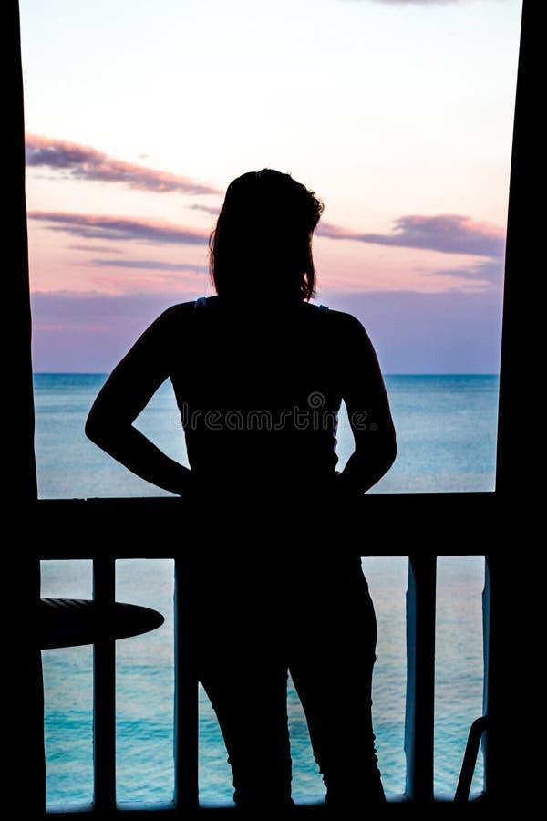 一个妇女身分的剪影在观看在海洋的阳台的太阳落山 免版税库存照片