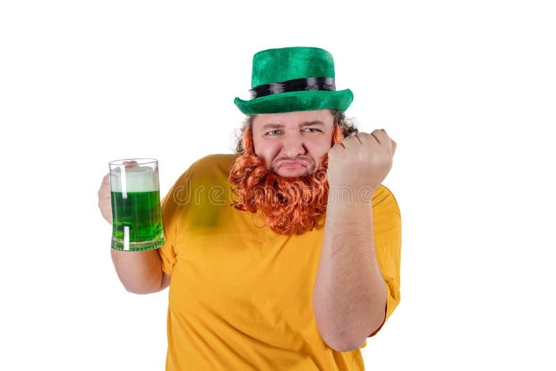 一个妖精帽子的一个微笑的愉快的肥胖人用在演播室的绿色啤酒 他庆祝圣帕特里克 免版税库存图片