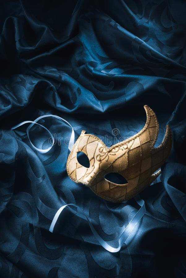 一个威尼斯式面具的大反差图象在蓝色织品的 库存图片