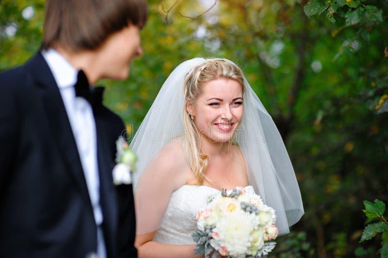 一个婚礼的微笑的新娘新郎在夏天户外 免版税库存图片