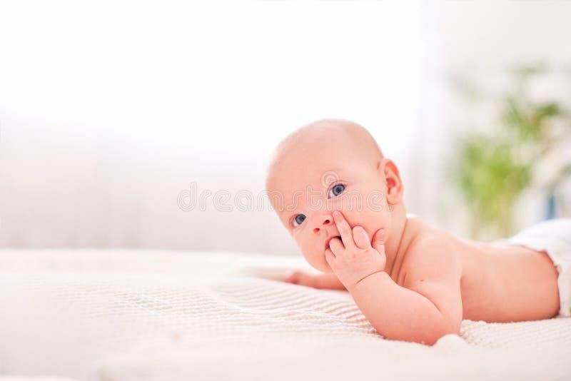 一个婴孩用在他的嘴的一只手 长牙齿对于儿童 吮反射 饥饿的矮小的婴孩 说谎在他的胃独自地举行 库存照片