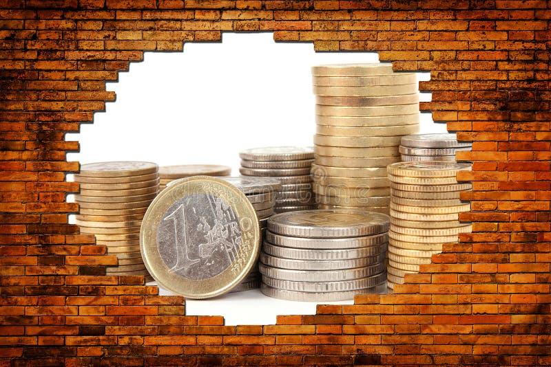 一个孔的金钱在砖墙 库存照片