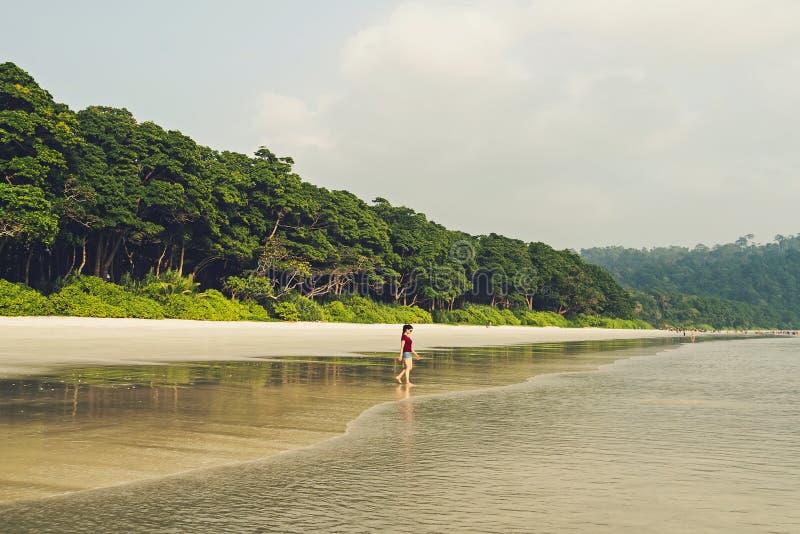 一个孤独的女孩沿海岛海岸线走 免版税库存照片
