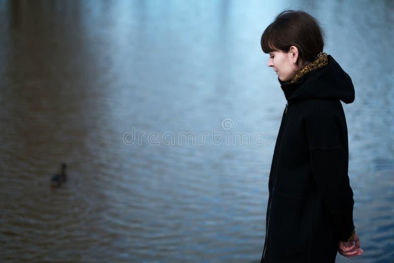 一个孤独的女孩的画象由湖的 免版税库存照片