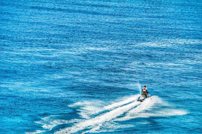 一个孤立喷气机滑雪者断裂在盛大土耳其人的镇静蓝色海洋水 免版税库存图片