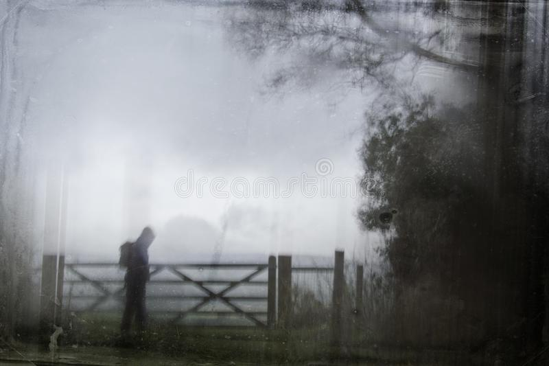 一个孤立戴头巾图的一个令人毛骨悚然的剪影与一个背包的由树围拢的门 一个黑暗,鬼的被弄脏的摘要,g 免版税库存图片