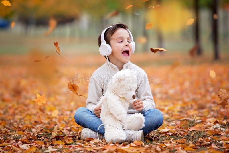 一个学龄前孩子的甜画象,与headph的听的音乐 库存图片