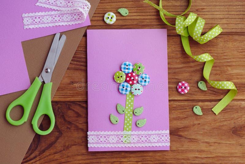 一个孩子做的好的贺卡为母亲节,父亲节,生日3月8日, 与一朵花的手工制造卡片从木按钮 免版税库存图片