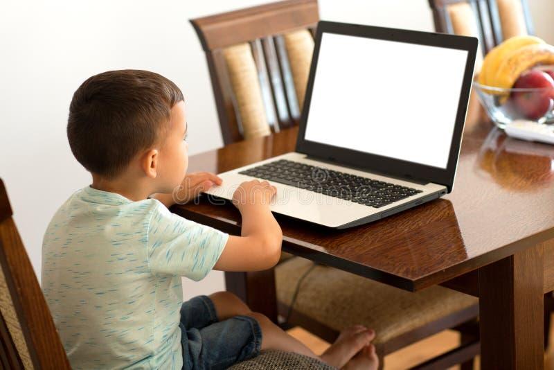 一个孩子和他的膝上型计算机在冒险 免版税库存图片