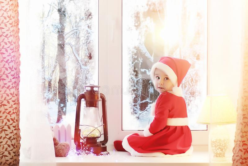 一个孩子在新年看窗口 孩子是waiti 免版税库存图片