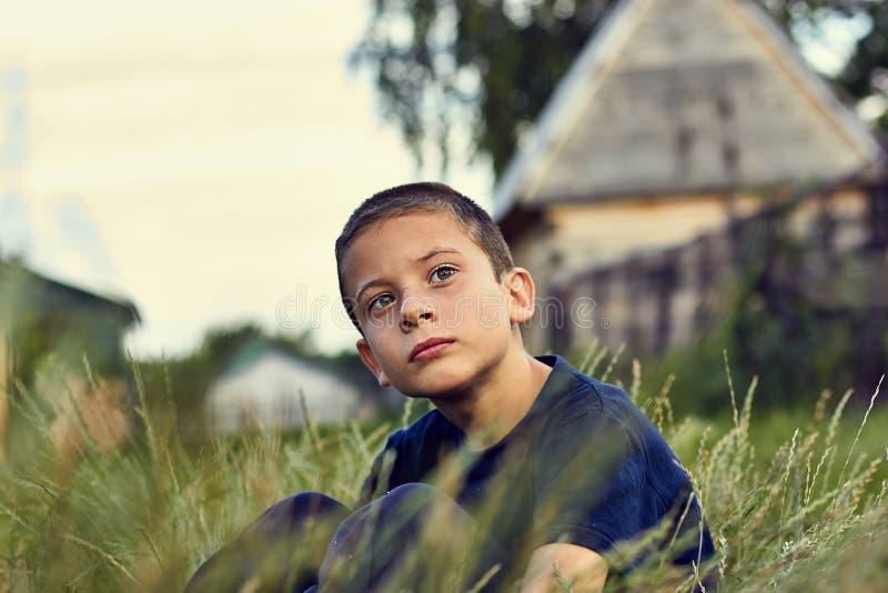 一个孩子的沉思和哀伤的神色有大脑麻痹的 夏天坐在草和调查的晚上男孩 免版税库存图片