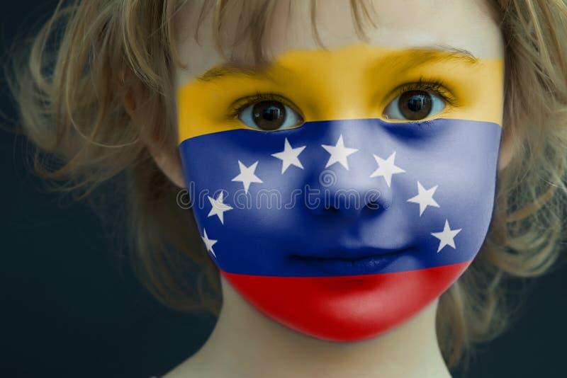 一个孩子的画象有一面被绘的委内瑞拉旗子的 免版税库存图片