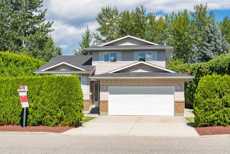 一个完善的邻里 大住宅房子大门有具体车道和绿色树篱的在前面 家庭房子为 图库摄影