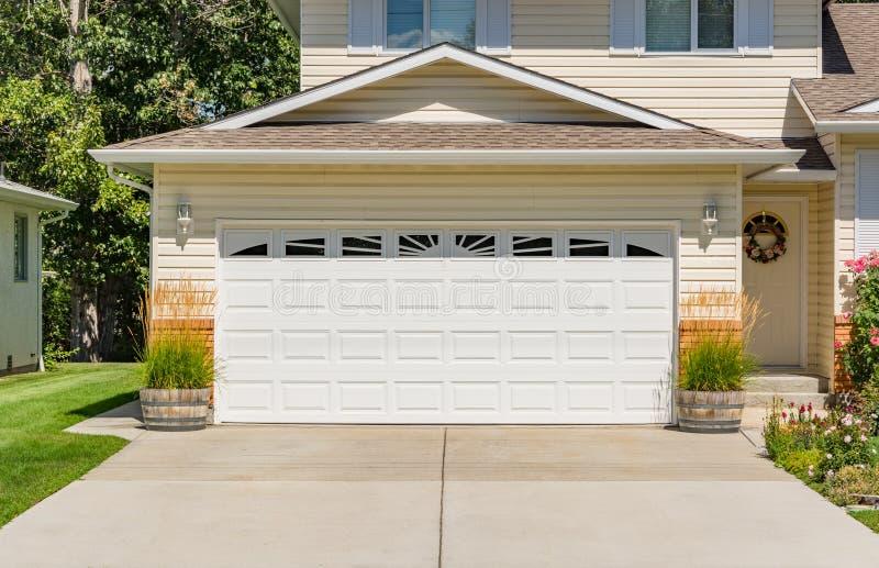 一个完善的邻里 有宽车库门的家庭房子和在前面的具体车道 免版税图库摄影