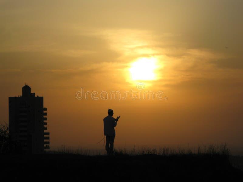 一个宗教信徒祈祷给小山的上帝在太阳和日落前面 免版税库存照片