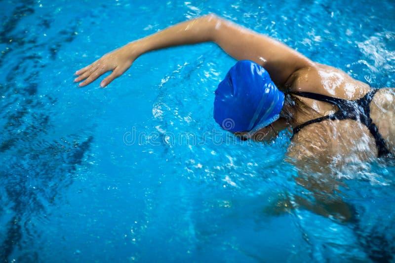 一个室内游泳池的女性游泳者-做爬行 库存图片