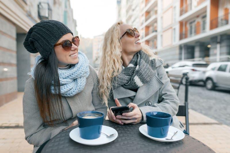 一个室外咖啡馆的两个年轻微笑的时髦的女人,饮用的咖啡,谈话,笑 都市的背景 库存照片