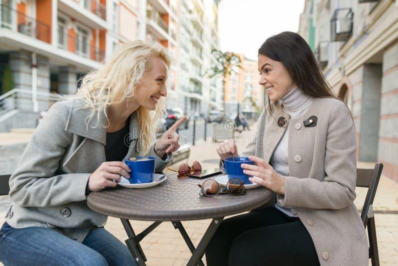 一个室外咖啡馆的两名年轻微笑的妇女,饮用的咖啡,谈话,笑 都市秋天背景 库存照片
